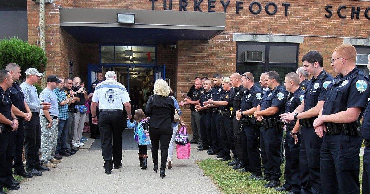Des policiers acclament la rentrée des classes d'une petite fille au papa décédé